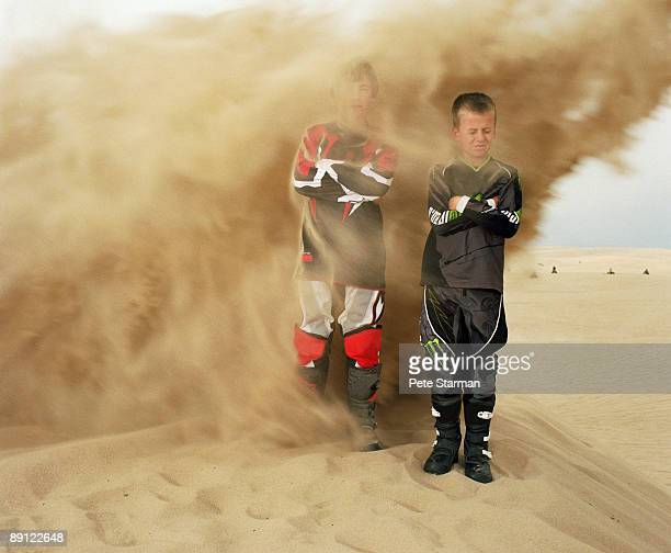 Two boys being blasted with sand from motorcycle.