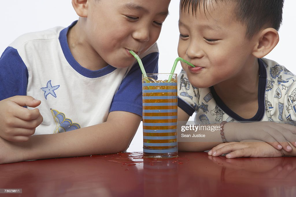 Two boys (4-6) blowing bubbles in drink : Stock Photo