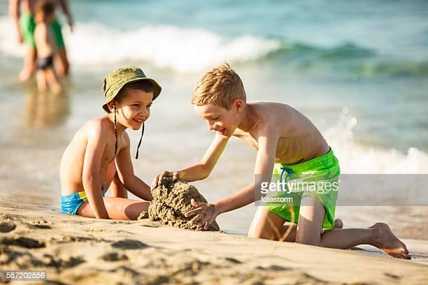 Two boys building sandcastles on beach