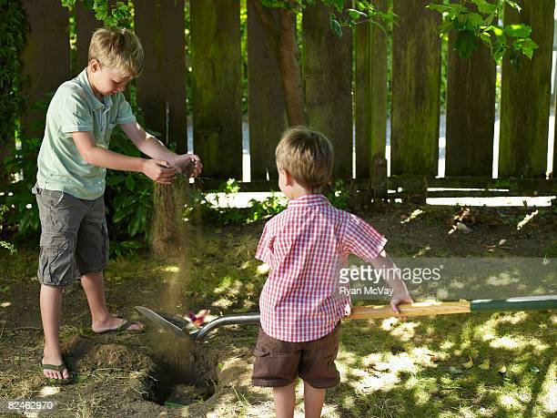 Two boys burying pet in hole in backyard