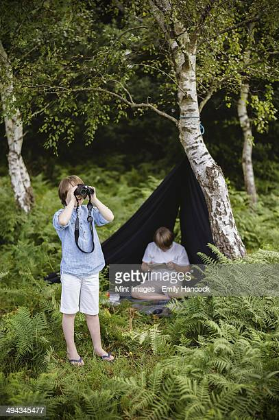 Two boys camping in the New Forest. One sitting under a black canvas shelter. One boy looking through binoculars.