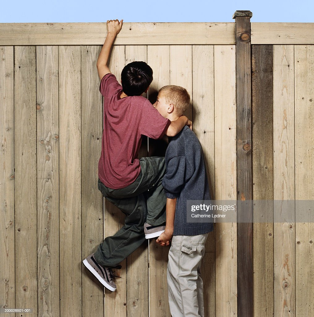 Two boys (10-12) cimbing over fence, one boy lifting the other : Stock Photo
