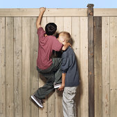 Two boys (10-12) cimbing over fence, one boy lifting the other