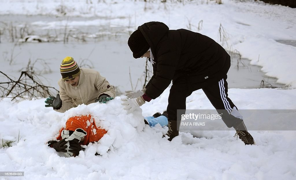 Two boys cover their aunt with snow, in the Northern Spanish village of Alsasua on February 25, 2013.