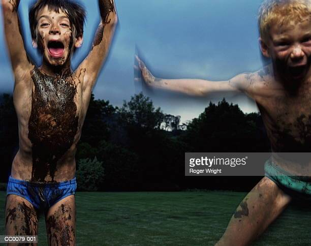 Two boys (5-7) covered in mud playing outdoors(digital composite)