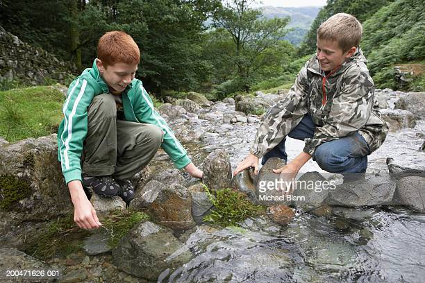 Two boys (11-13) crouching by stream