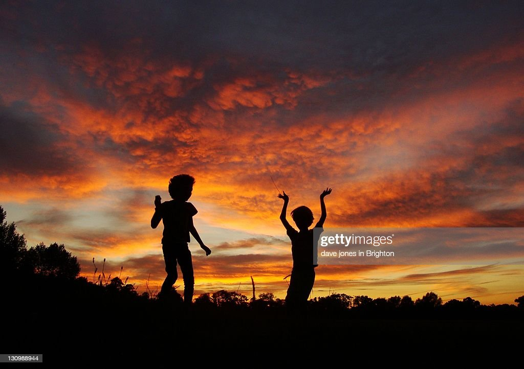 Two boys dance for joy after day at beach