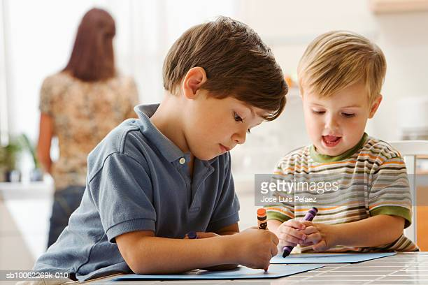 Two boys (3-7) drawing on table, mother in background