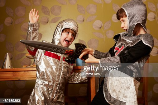Two boys dressed as knights playing with toy sword : Stock Photo