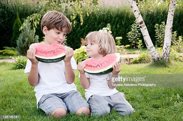 Two boys eating watermelon slices