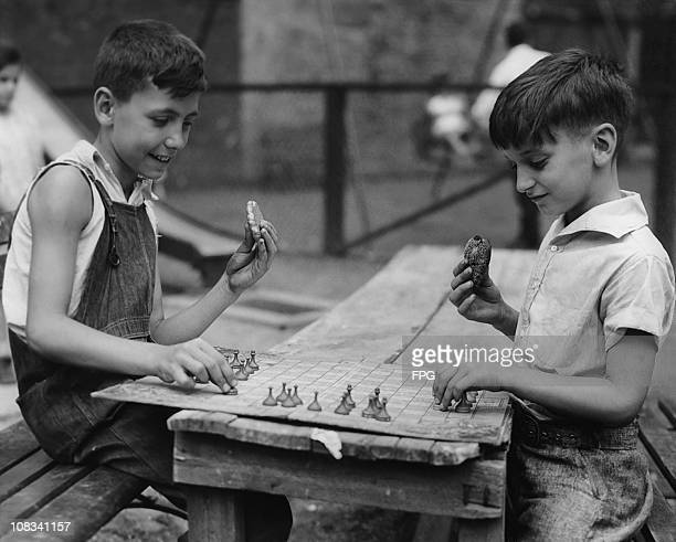 Two boys eating while they play draughts or checkers circa 1950