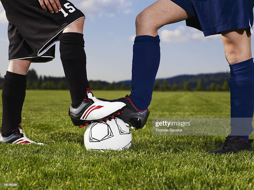 Two boys (10-13) facing, standing on football in field, low section : Stock Photo