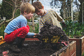 Two boys filling plastic toy truck with mud in the garden
