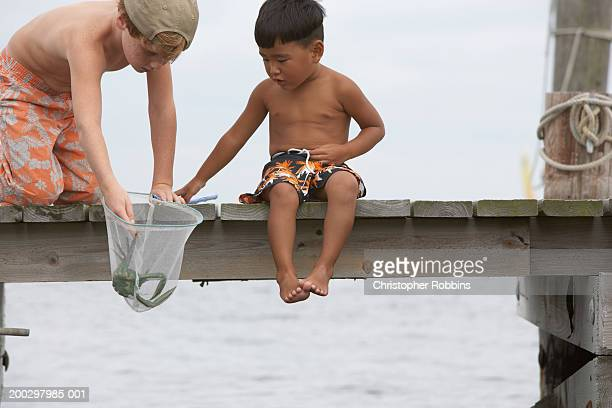 Two boys (3-7) fishing on jetty, looking in fishing net, close-up