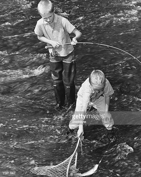 Two boys fishing; one catching fish in net