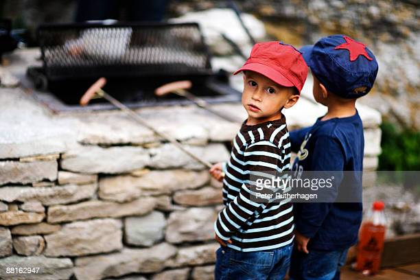 Two boys grilling hot dogs Sweden.
