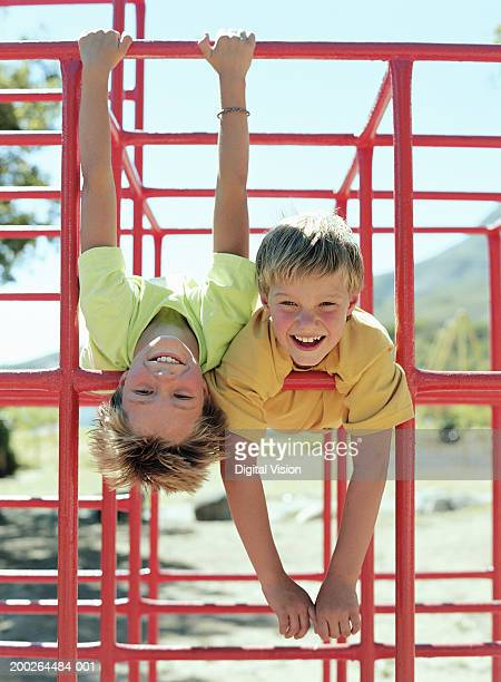 Two boys (9-11) hanging on bars in playground, smiling, portrait