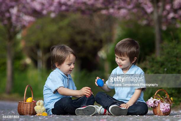 Two boys, having fun with easter eggs in the park