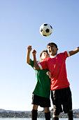 Two boys heading football, eyes closed