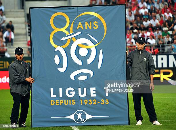 Two boys hold the League 1 official flag as part of the 80th anniversary of the French football professional League prior to the French L1 football...