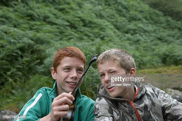 Two boys (11-13) holding up leech on stick
