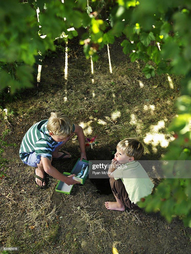 Two boys in backyard burying pet bird