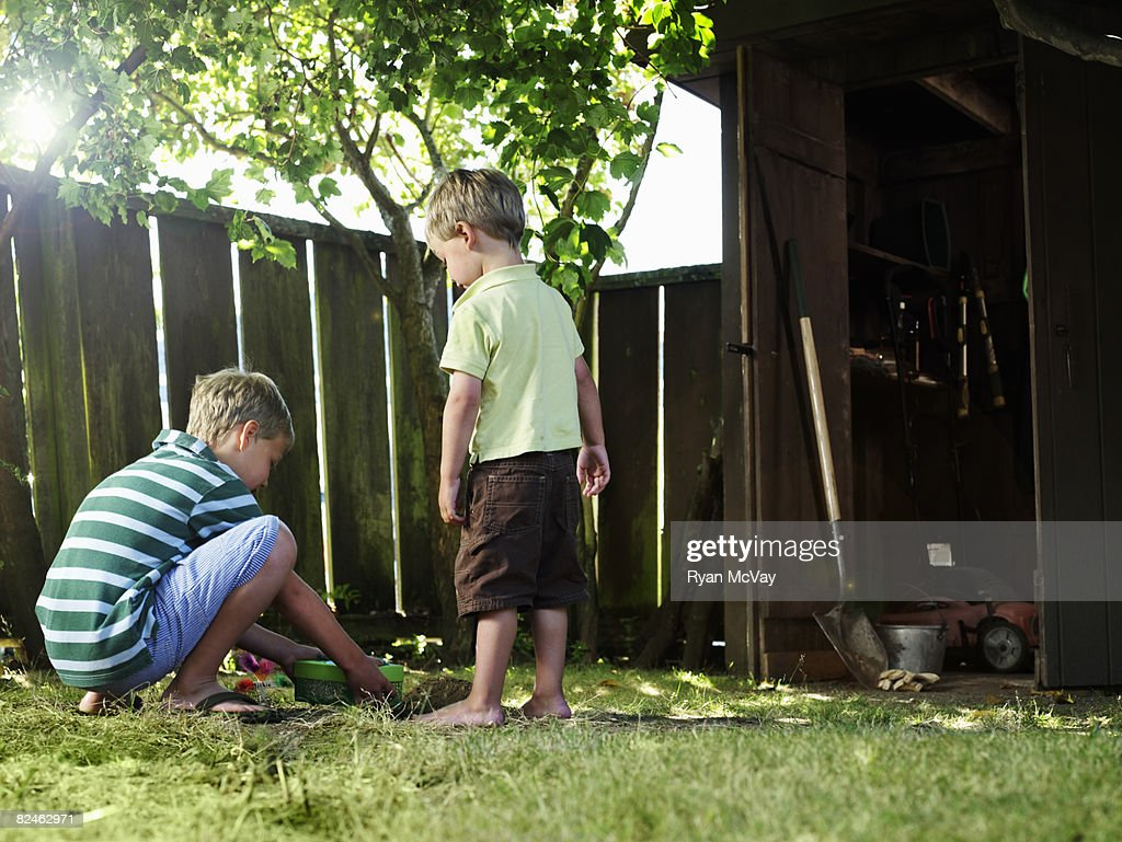 two boys in backyard burying pet stock photo getty images