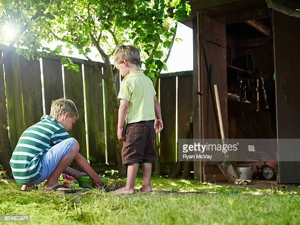 Two boys in backyard burying pet