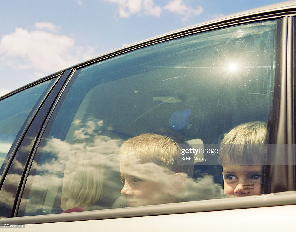 Two boys (4-9) in car, looking through window : Stock Photo