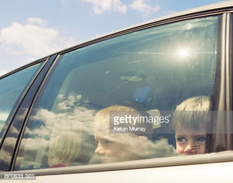 Two boys (4-9) in car, looking through window : Photo