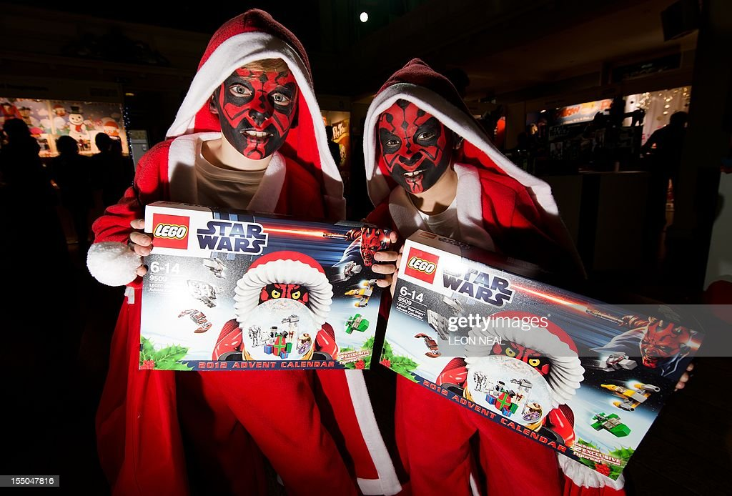 Two boys in festive costumes with their faces painted like the Star Wars character Darth Maul pose with the Lego Star Wars advent gift calendar at the 2012 'Dream Toys' exhibition in central London on October 31, 2012. The annual event sees the toy industry attempt to predict what will be the top twelve toys of the Christmas season. AFP PHOTO / LEON NEAL