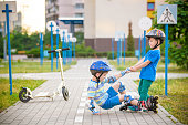 Two boys sibling brothers together in park, helps boy with roller skates to stand up after fall. Friendship and active leisure summer holidays time with family concept.