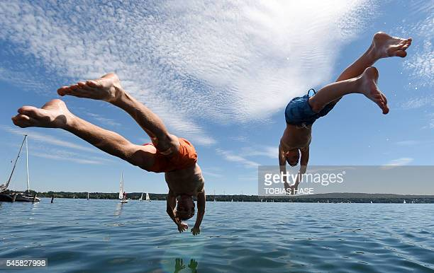 Two boys jump into the water of the Starnberger See lake in Starnberg southern Germany on July 10 2016 / AFP / dpa / Tobias Hase / Germany OUT