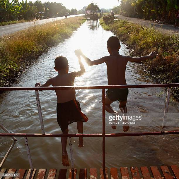 Two boys jumping from bridge