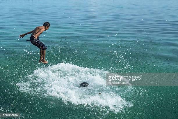 Two boys jumping into the sea, Salakan Island, Semporna, Sabah, Malaysia
