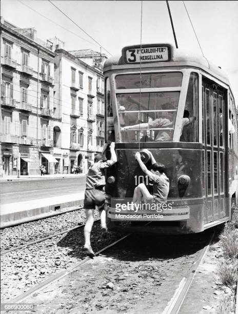 Two boys jumping sneakily on a tram This picture is taken from the monography 'Mario De Biasi Il mio sogno Š qui' curated by Enrica Vigan• published...
