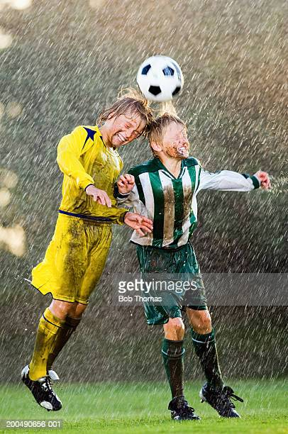 Two boys (11-13) jumping to head football in rain