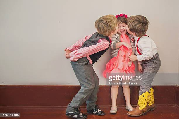 Two boys kissing a girl on the cheek