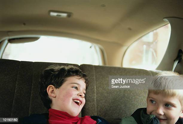 Two boys (6-8 years) laughing in car