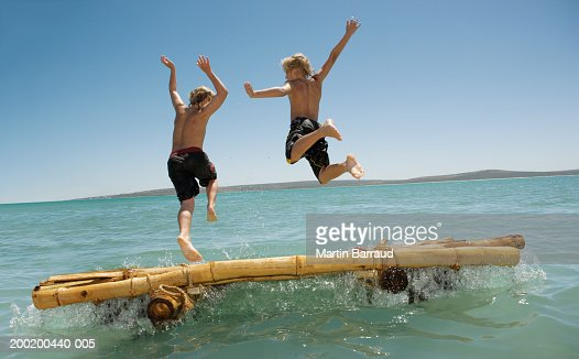 Two boys (10-12) leaping off bamboo raft into sea, rear view