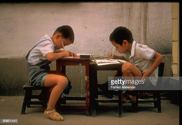 Two boys learning to write Chinese characters at low table in school