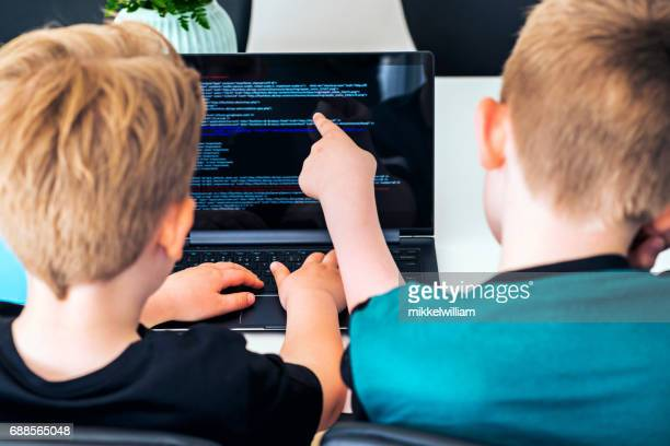Two boys learns to code on laptop computer and help each other