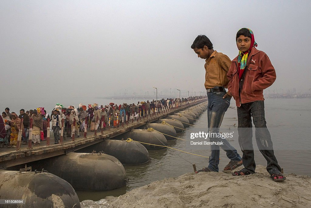 Two boys look out over a pontoon bridge as pilgrims cross over near to Sangam, the confluence of the holy rivers Ganges, Yamuna and the mythical Saraswati, during the Maha Kumbh Mela on February 12, 2013 in Allahabad, India. The Maha Kumbh Mela, believed to be the largest religious gathering on earth is held every 12 years on the banks of Sangam, the confluence of the holy rivers Ganga, Yamuna and the mythical Saraswati. The Kumbh Mela alternates between the cities of Nasik, Allahabad, Ujjain and Haridwar every three years. The Maha Kumbh Mela celebrated at the holy site of Sangam in Allahabad, is the largest and holiest, celebrated over 55 days, it is expected to attract over 100 million people.