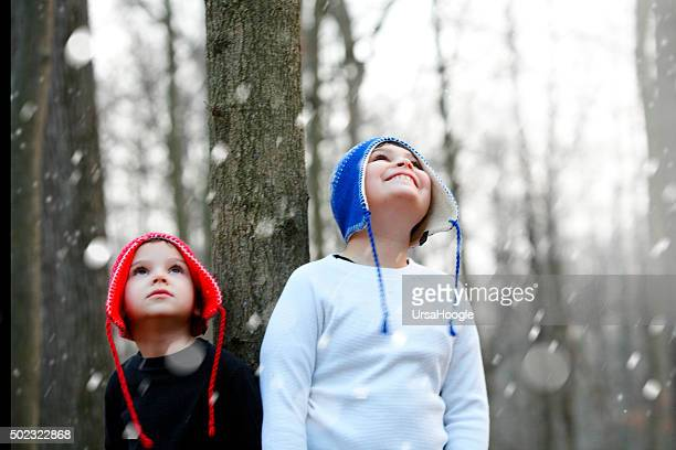 Two boys looking up full of wonder at falling snow