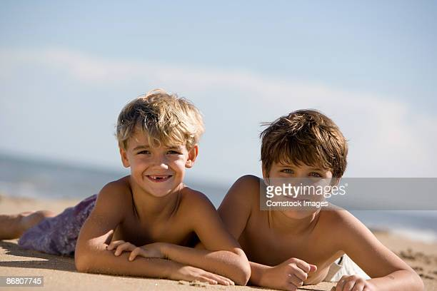Two boys lying in the sand