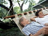 Two boys (6-8) lying on hammock, smiling