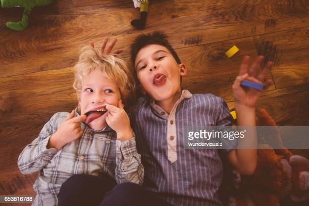 Zwei jungen, die lustige Grimassen beim Spielen auf dem Boden