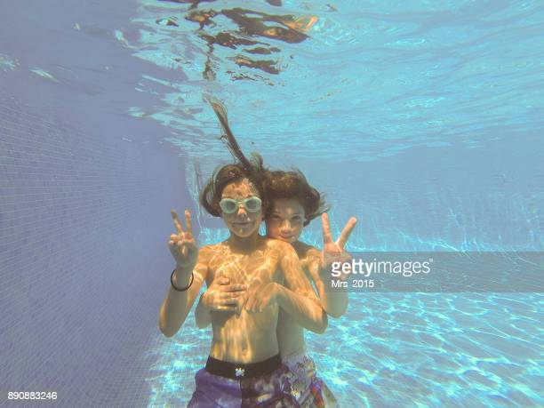 Two boys making v signs underwater in a swimming pool
