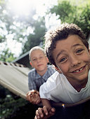 Two boys (6-8) on hammock, smiling, portrait