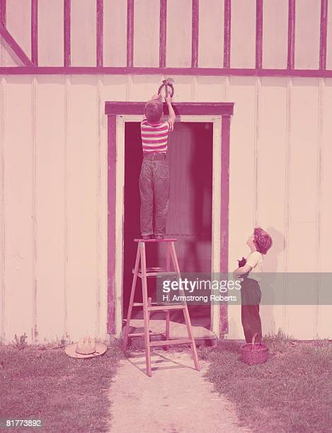 Two boys on ladder fixing good luck horseshoe over barn door, girl holding kitten. (Photo by H. Armstrong Roberts/Retrofile/Getty Images)